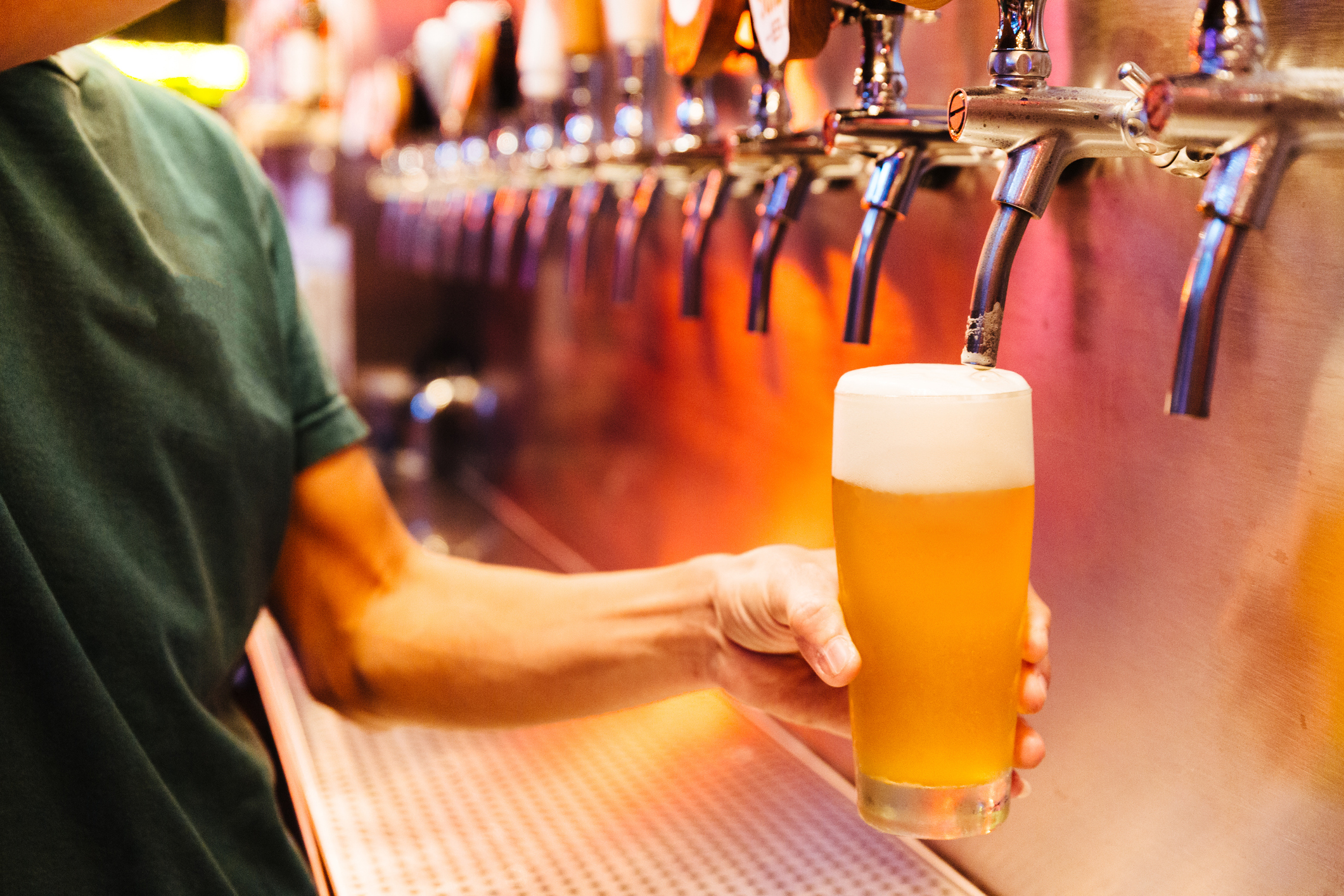 a person pouring beer in a bar